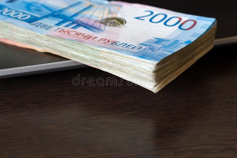 Payments for computer work concept. Stack of russian rubles lay on laptop keyboard. Wooden table with copy space. Payments for computer work concept. Stack of stock images