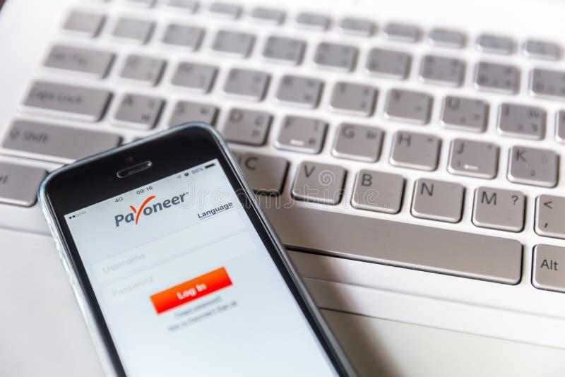 Payoneer på iPhone med datorbärbar datorbakgrund royaltyfria bilder