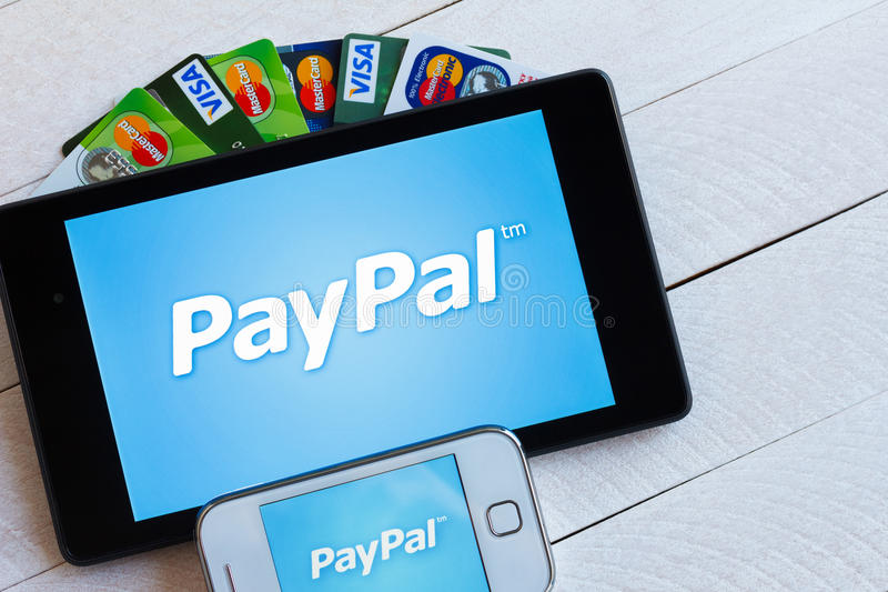 PayPal在片剂和智能手机的付款系统商标 免版税图库摄影