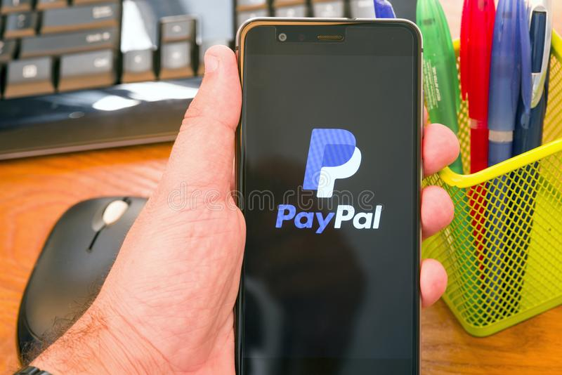 Paypal logo. PIATRA NEAMT, ROMANIA - JULY 30, 2018: Hand holds a mobile phone with PayPal on the screen, office background royalty free stock images