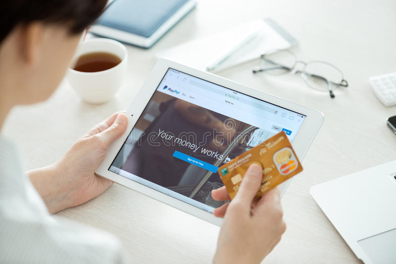Paypal website on Apple iPad Air. KIEV, UKRAINE - JUNE 27, 2014: Person with credit card in hand looking on a brand new Apple iPad Air with Paypal website on a royalty free stock photography