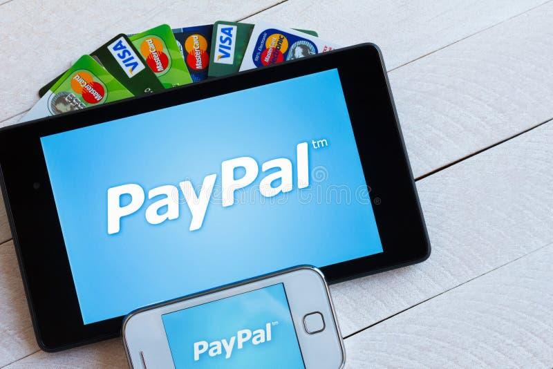 Paypal-Zahlungssystemlogo auf Tablette und Smartphone lizenzfreie stockfotografie