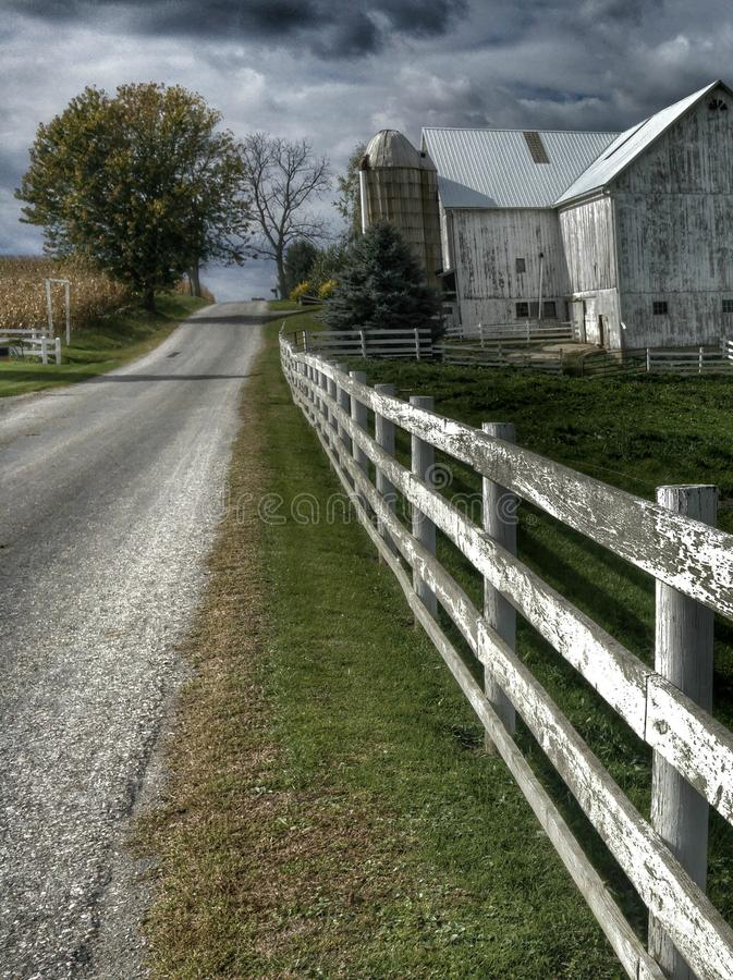 Pays amish de l'Ohio avec une grange et une barrière blanche image stock
