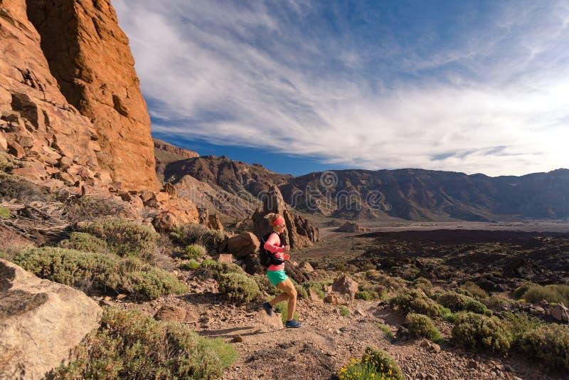 Pays croisé fonctionnant avec le sac à dos en montagnes sur la traînée rocheuse photographie stock