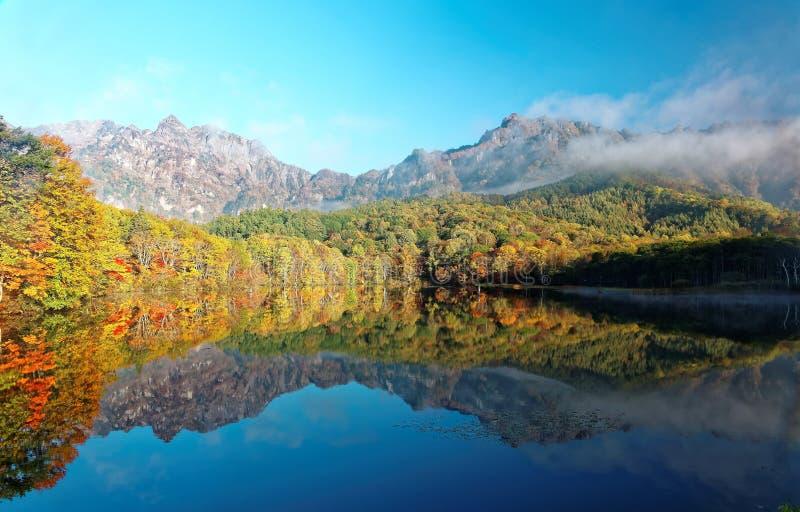 Paysage étonnant de lac d'automne de Kagami Ike Mirror Pond dans la lumière de matin avec des réflexions symétriques de feuillage photographie stock libre de droits