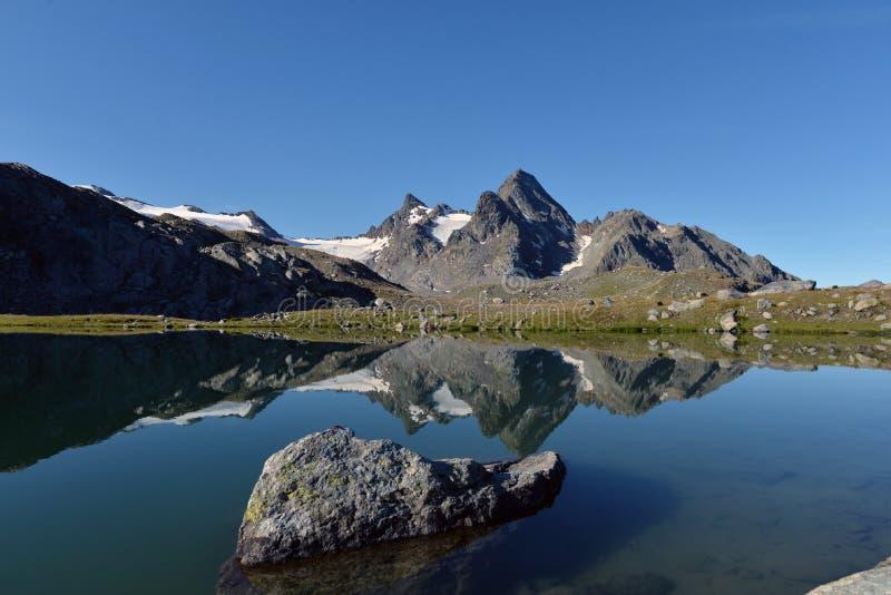 Paysage alpin italien et lac clair comme de l'eau de roche reflétant les crêtes photographie stock libre de droits