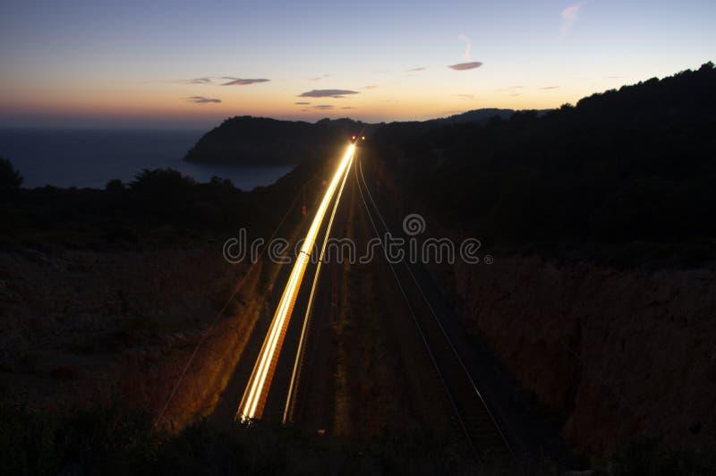 Paysage au crépuscule à côté de la côte méditerranéenne avec la lumière de train se déplaçant entre deux tunnels photos stock