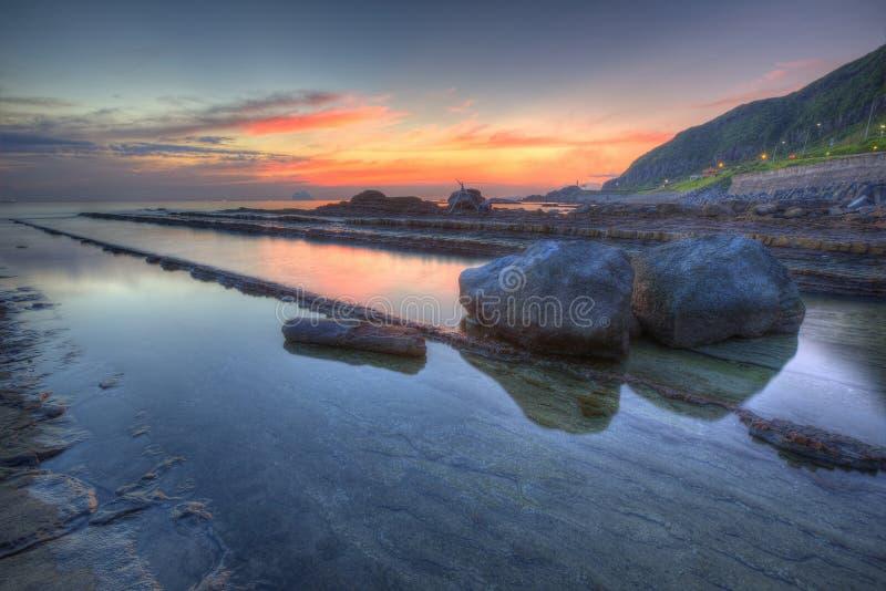 Paysage au lever du soleil d'une côte rocheuse dans le nord de Taïwan, avec de belles reflets de soleil doré image libre de droits