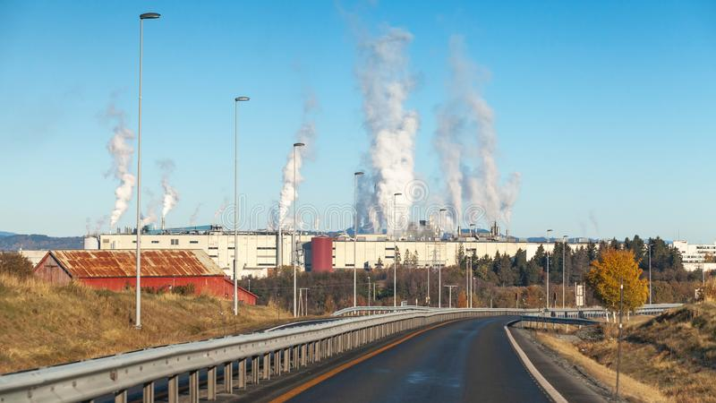 Paysage avec de la fumée au-dessus de l'usine de fabrique de pâte à papier images libres de droits