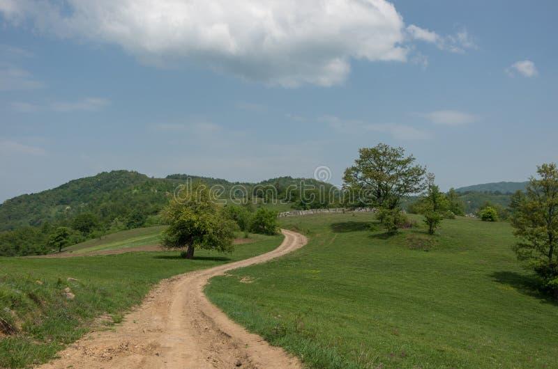 Paysage avec des collines, des prés et le chemin de terre sur la montagne mA de Radan photos libres de droits
