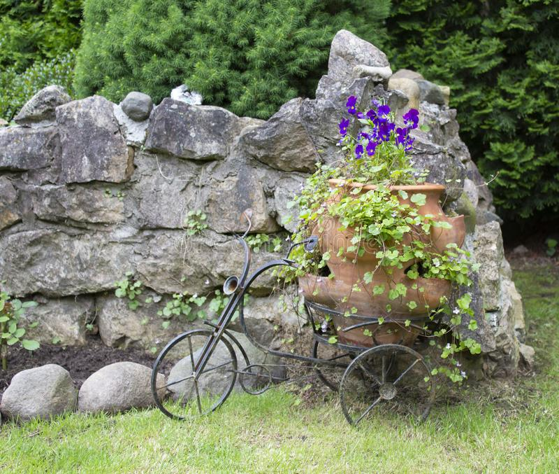 Paysage avec des pensées dans un grand pot et une bicyclette décorative photo stock