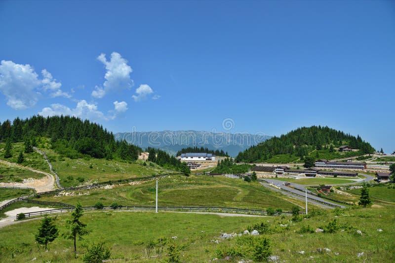 Paysage avec la base de biathlon à la station de vacances de Fundata chez Cheile Gradistei avec des montagnes de Piatra Craiului  image stock