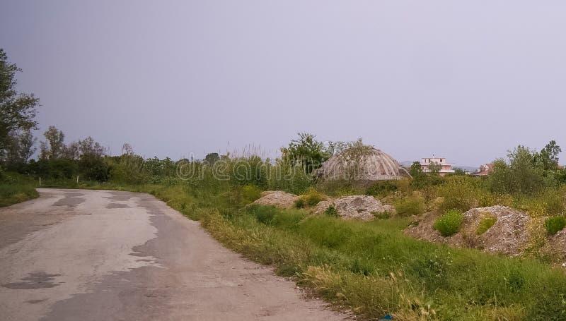 Paysage avec les soutes militaires au milieu de l'champs ruraux, Apollonia, Fier, Albanie photo libre de droits