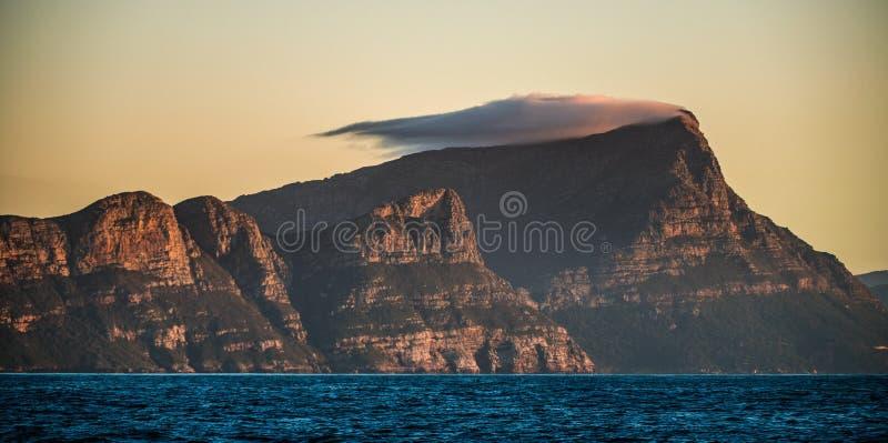 Paysage avec montagnes, nuages et océan Panorama de montagnes, nature sauvage au coucher du soleil ou au lever du soleil photographie stock libre de droits