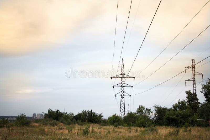 Paysage avec plusieurs lignes électriques puissantes dans la perspective d'un champ fauché de blé et d'un ciel nuageux de coucher photographie stock libre de droits