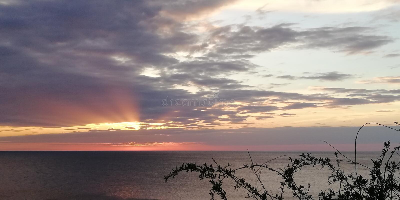 Paysage contrastant marin de coucher du soleil Les rayons du coucher de soleil percent les nuages Fond photos libres de droits