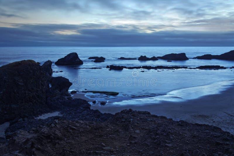 Paysage déprimé de côte de l'océan pacifique au coucher du soleil avec des tons bleus images stock