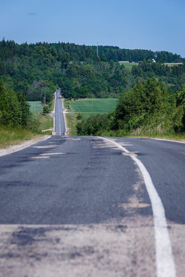 Paysage d'été avec la route asphaltée allant en bas de la cavité photographie stock