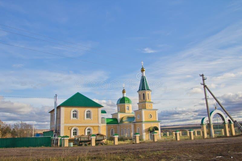 Paysage d'automne avec des nuages au-dessus de l'église de village images libres de droits