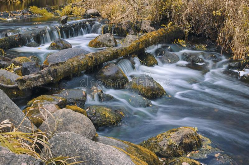 Paysage d'automne avec une rivière coulant sans à-coup entre les rochers images libres de droits