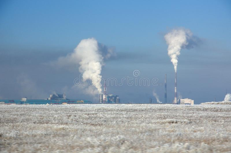 Paysage d'hiver avec l'usine métallurgique avec de la fumée lourde des tuyaux derrière un champ couvert d'herbe sèche congelée so images libres de droits