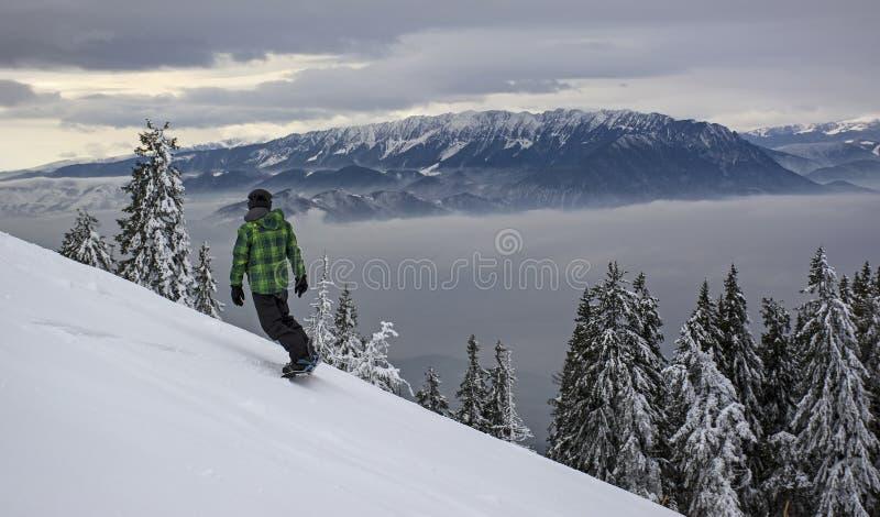Paysage d'hiver avec la forêt de sapins couverte par la chute de neige importante en montagne de Postavaru, station de vacances d photographie stock