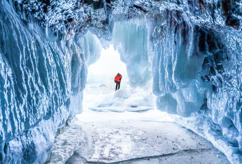 Paysage d'hiver, caverne de glace congelée avec le jeune photographe seul se tenant Déplacement en hiver photos libres de droits