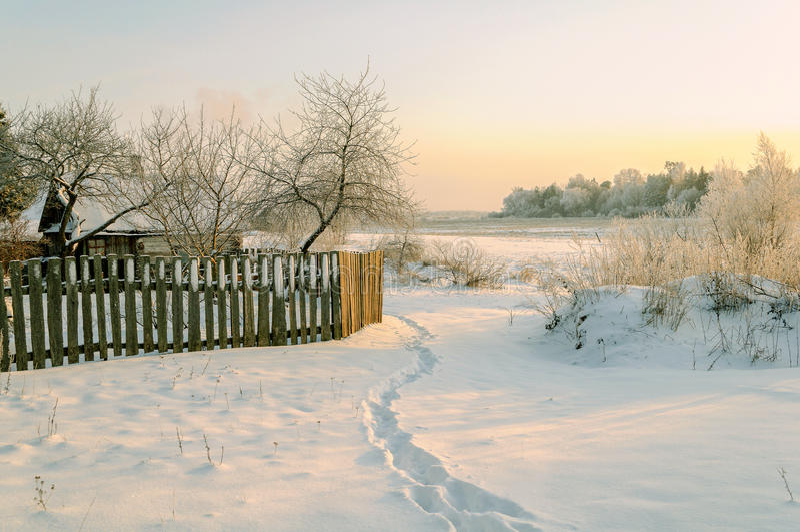Paysage d'hiver - scène d'hiver avec la maison et la barrière en bois parmi les arbres givrés et la nature d'hiver au coucher du  photographie stock libre de droits
