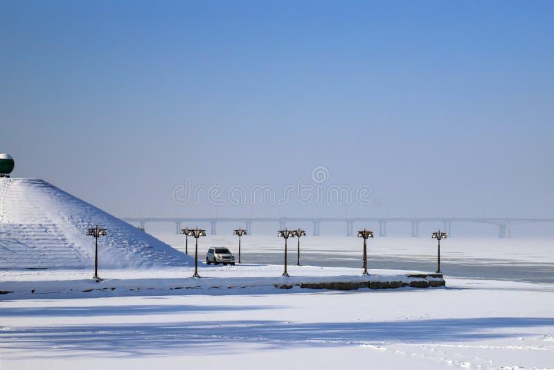 Paysage d'hiver d'une rivière couverte de la glace et de neige, une promenade avec des lanternes de cru et une pyramide Paysage u photos stock