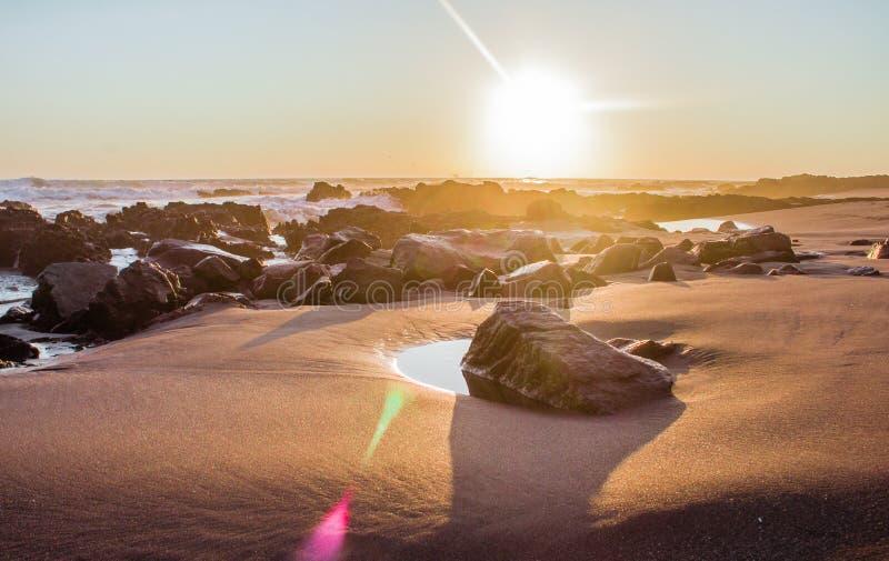 Paysage d'une plage avec des roches pendant le coucher du soleil photographie stock libre de droits