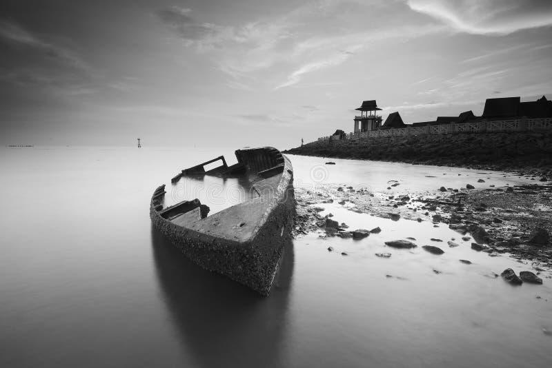 Paysage de bateau échoué avec des morceaux de silhouette de pièce de bateau et de ciel vibrant de coucher du soleil photos libres de droits