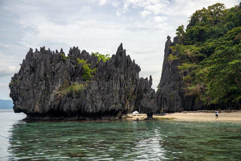 Paysage de bord de la mer avec la plage blanche de sable et la falaise noire Vue tropicale de littoral d'île de Palawan, les Phil photographie stock