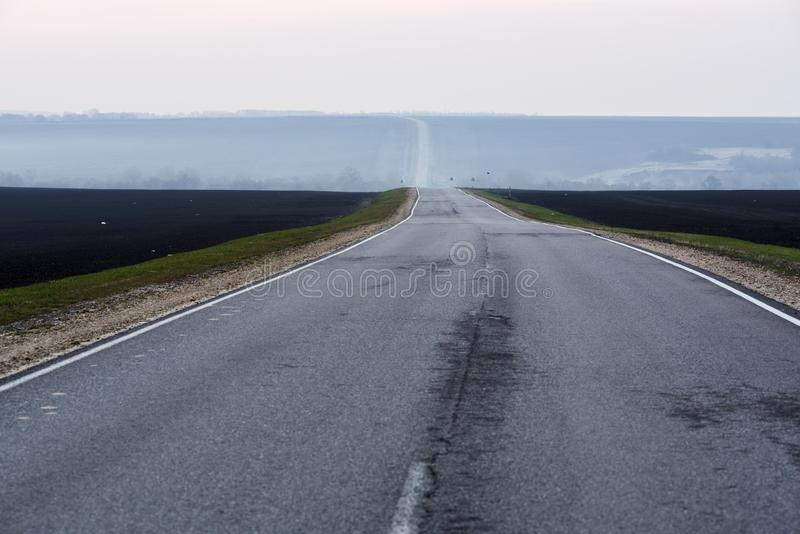 Paysage de campagne Route vide allant à l'horizon dans le matin renfrogné image libre de droits