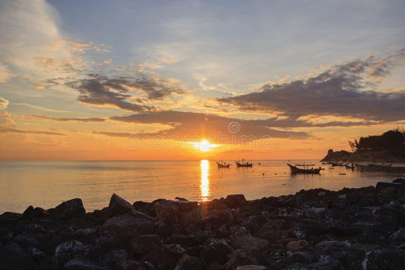 Paysage de ciel et de mer qui a le groupe du petits bateau de pêche et brise-lames à l'aube photos libres de droits
