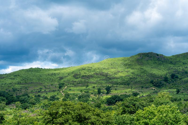 Paysage de colline à la lumière du soleil contre le ciel avec des nuages de tonnerre photo stock