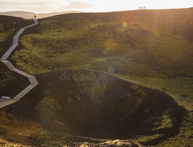 Paysage de cratère volcanique moussu vert luxuriant, ou caldeira, et escaliers en bois avec les touristes rétro-éclairés images stock