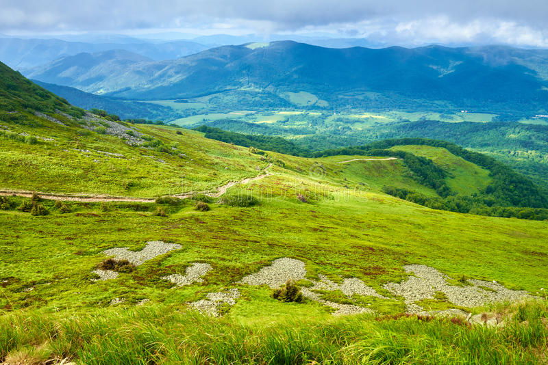 Paysage de flanc de montagne de pré de vert de panorama de montagnes photos libres de droits