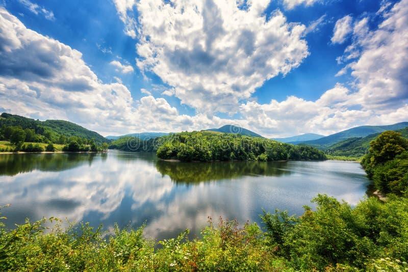 Paysage de jour de bel été, méandre de la rivière avec la réflexion, collines vertes et montagnes et ciel nuageux bleu renversant photos libres de droits