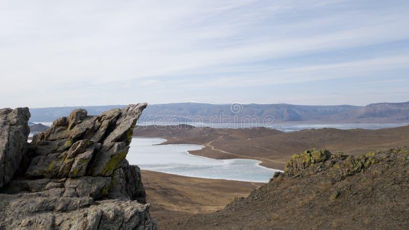 Paysage de la partie du sud de l'île d'Olkhon en Sibérie Terrain montagneux, steppes et lac Baïkal congelé image libre de droits