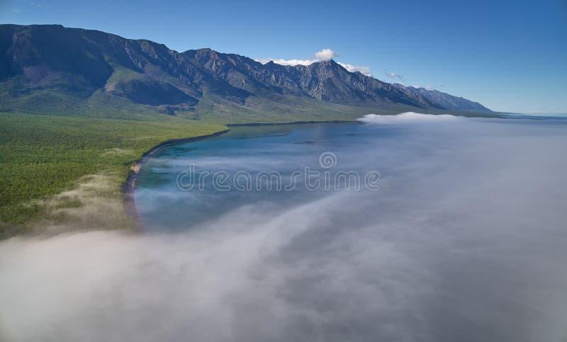 Paysage de lac mountain avec le soleil brillant à la brume rocheuse de matin au-dessus du lac photo libre de droits