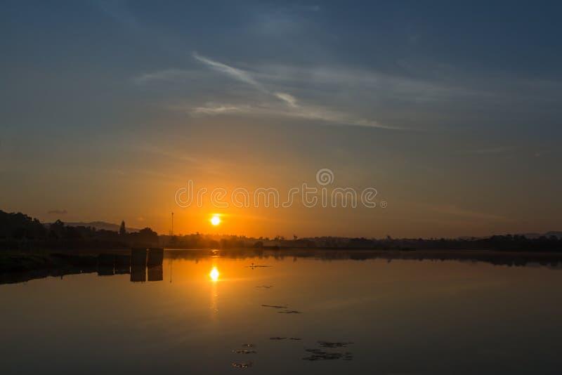 Paysage de lever de soleil de réflexion avec le lac fini nuageux pendant le matin de la Thaïlande image libre de droits