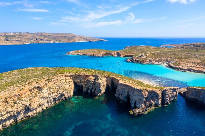 Paysage de Malte Littoral d'île de Comino d'en haut Silhouette d'homme se recroquevillant d'affaires Cavernes bleues de lagune et photographie stock libre de droits