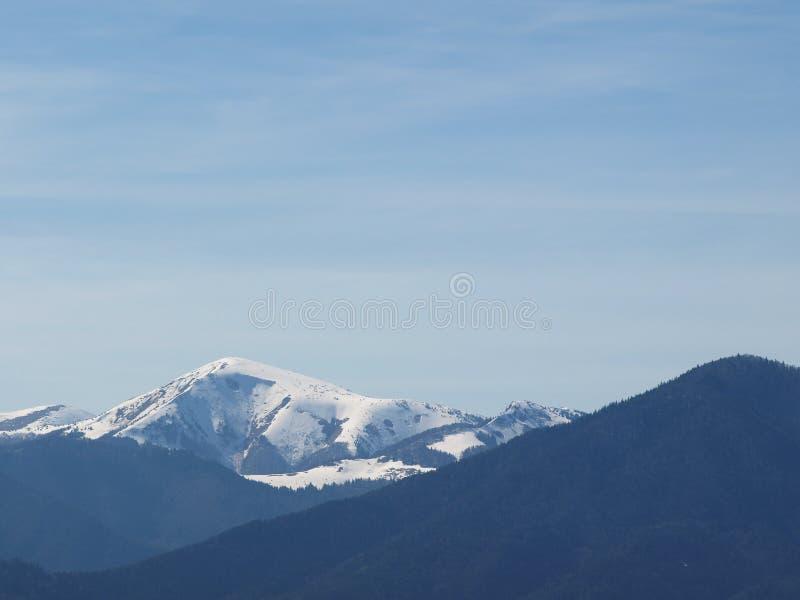 Paysage de matin avec les montagnes et le ciel bleu Même le coucher du soleil sur l'horizon des collines avec la neige et le nuag photos stock