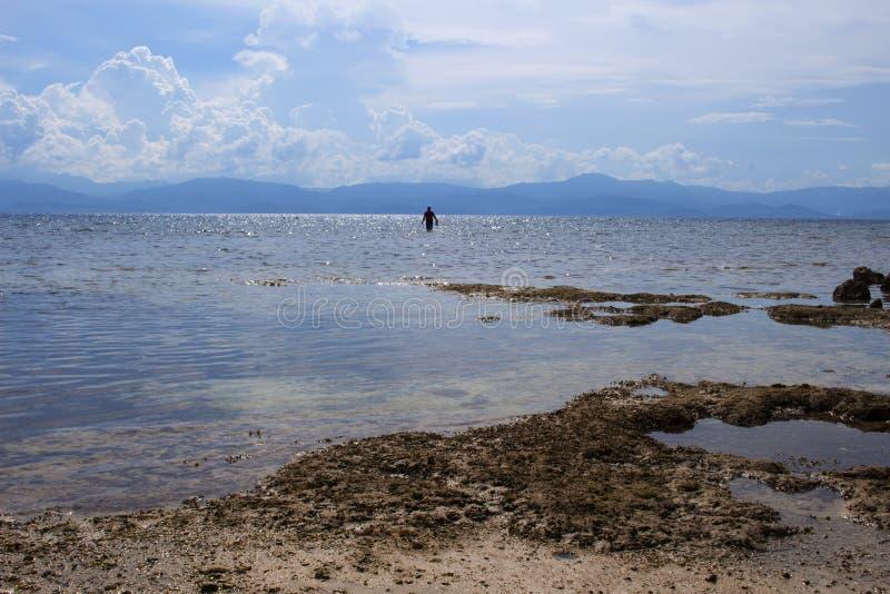 Paysage de mer avec la silhouette de pêcheur Paysage marin avec l'île éloignée image libre de droits