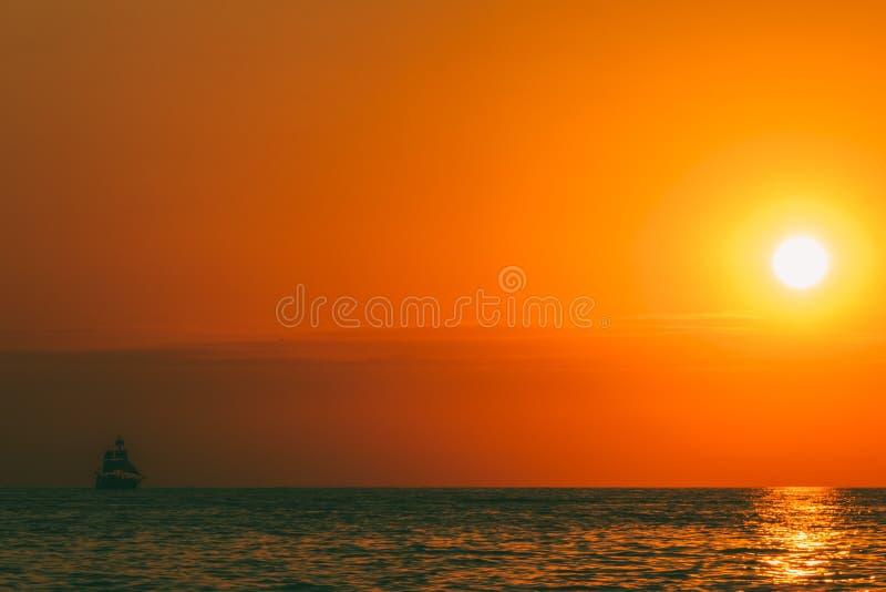 Paysage de mer avec un coucher de soleil et un voilier photo libre de droits