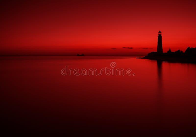 Paysage de mer dans des tons rouge foncé avec la silhouette d'un bateau submergé et d'un vieux phare Paysage marin dans la couleu photos stock