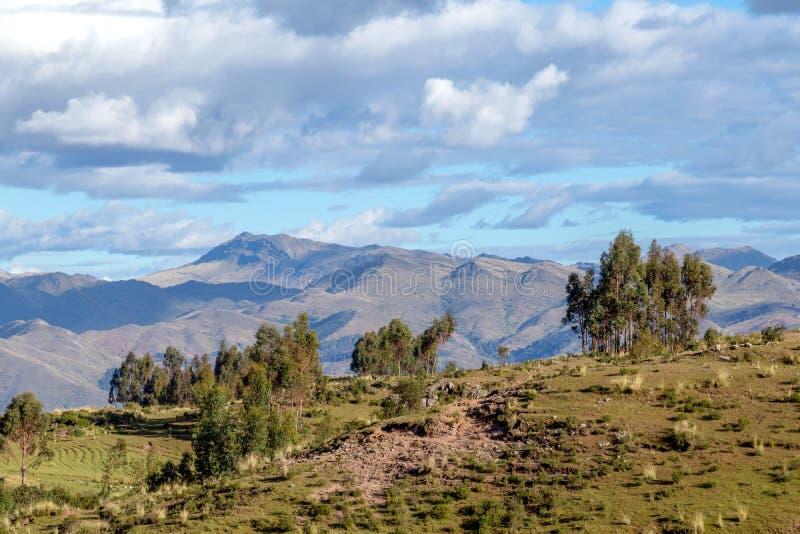 Paysage de montagne avec la vallée fertile au-dessous des forêts raides et des terrasses agricoles antiques au coucher du soleil photographie stock libre de droits