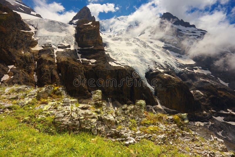 Paysage de montagne avec les glaciers et la station de vacances voisine de crêtes de Kandersteg images libres de droits