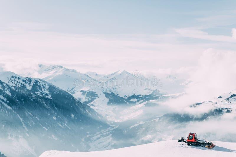 Paysage de montagne d'hiver avec la machine de toilettage de neige photos stock
