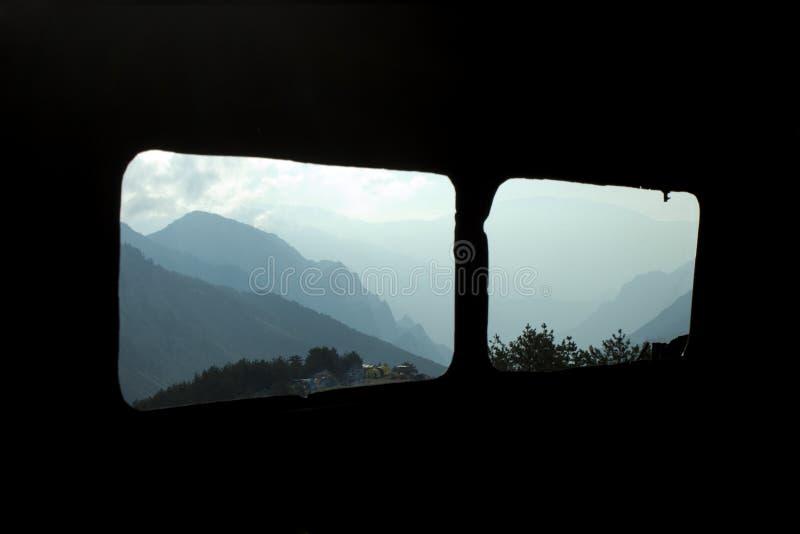 Paysage de montagne d'une fenêtre de voiture abandonnée images stock